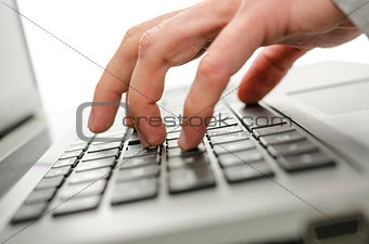 Male hand typing on laptop