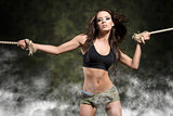 fitness woman with tied arms with smoke and military shorts