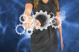 Busineswoman touching graphic wheels and cogs