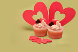 Two valentines cupcakes with five heart decorations