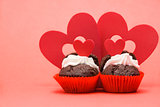 Two valentines cupcakes with four heart decorations