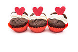 Three chocolate valentines cupcake with heart decorations and cream