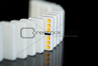 One yellow domino in a line of white ones
