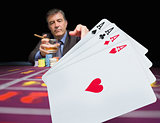 Gambler holding whiskey at poker table with digital hand of cards in foreground
