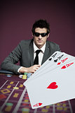 Gambler in sunglasses with digital four aces in foreground