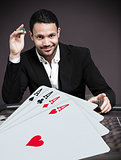Handsome gambler betting on four aces at poker table