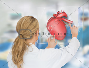 Blonde doctor consulting heart diagram on touchscreen display