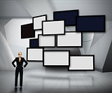 Group of blank screens on grey background with businesswoman looking up