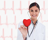 Doctor holding stethoscope up to red heart graphic