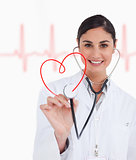 Happy doctor holding up stethoscope to red heart design