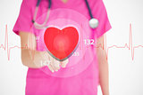 Nurse in pink scrubs touching red ECG line with heart graphic