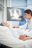 Doctor checking pulse of elderly patient beside screen displaying chest xray