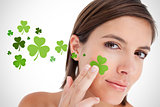 Smiling woman touching shamrocks to face