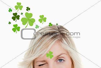 Blonde woman winking on shamrock background