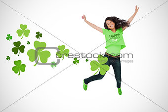 Girl wearing patricks day tshirt jumping for joy