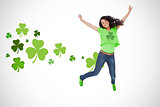 Girl wearing green shamrock tshirt jumping for joy