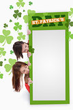 Girls holding blank green placard with patricks day text