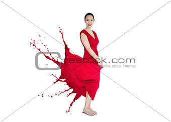 Asian woman smiling with red dress turning to paint splatter