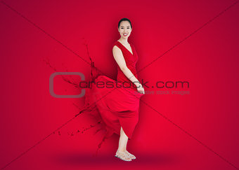 Asian woman with red dress turning to paint splatter