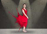 Happy asian woman with red dress turning to paint splatter on stage