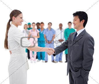 Business people shaking hands with medical staff in background