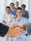 Businessmen shaking hands with team behind them