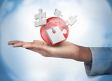 Hand with digital white puzzles and a red globe