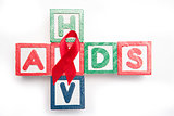 Wood blocks spelling aids and hiv in a cross shape with red awareness ribbon