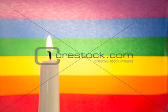 Candle against rainbow flag