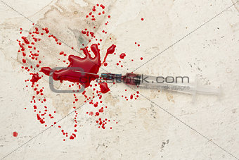 Syringe lying on floor with blood