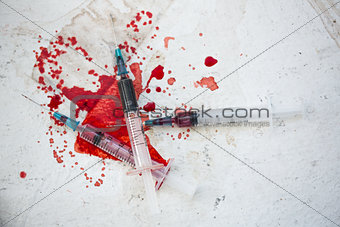 Three syringes in pool of blood