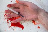 Lifeless hand holding bloody syringe