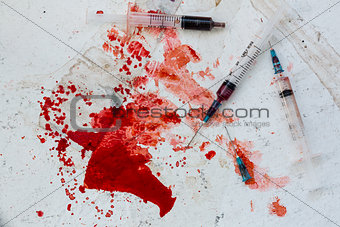 Three syringes lying on blood splatter