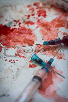 Two syringes lying on blood splatters