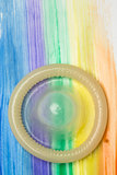 Rolled up condom on rainbow brush stroke
