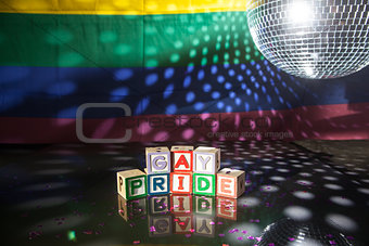Block spelling gay pride under light of disco ball