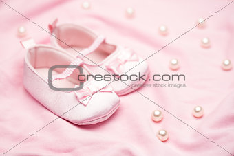 Baby girls pink booties on pink blanket