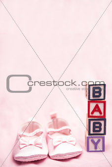 Baby girls pink booties beside blocks spelling baby