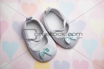 Baby blue booties on heart pattern background