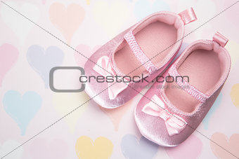 Baby pink booties on heart pattern background