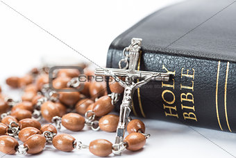 Black leather bound holy bible with rosary beads