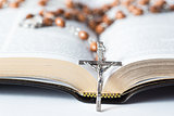 Cross of rosary beads resting against bible