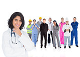 Doctor smiling with various workers behind her