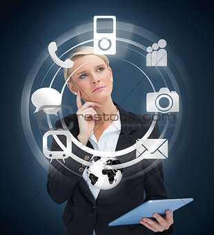 Thoughtful businesswoman with tablet pc considering various applications