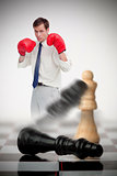 Businessman in boxing gloves knocking over chess pieces