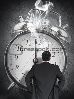 Businessman looking at smoking clock