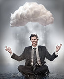 Businessman meditating under cloud
