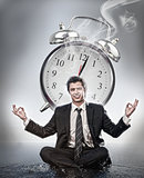 Businessman meditating in front of alarm clock