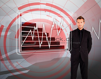 Businessman standing against graph display