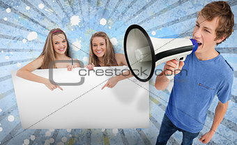 Pretty girls pointing to blank card with young man shouting through megaphone